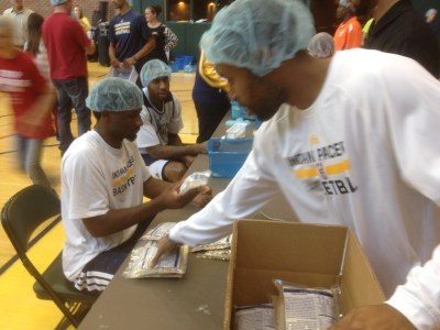 From left to right, Solomon Hill, Rasual Butler, and C.J. Watson wear fashionable headgear as they prepare meals for 60,000.