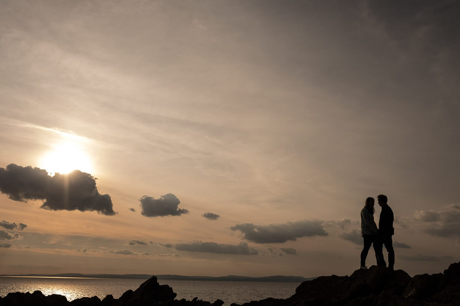 Engaged couple in silhouette at Clevedon beach