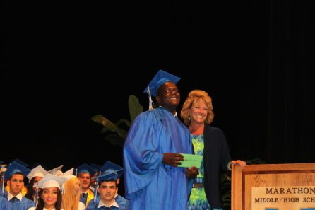 Thomas Lancaster celebrates with Assistant Principal Liz Logan upon learning he earned the $8,000 Voices for the Florida Keys Children Carol Parker Scholarship.