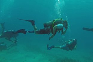 A diver from CWVC tests the capabilities of his prosthetic leg underwater, while another dives without the prosthetics.