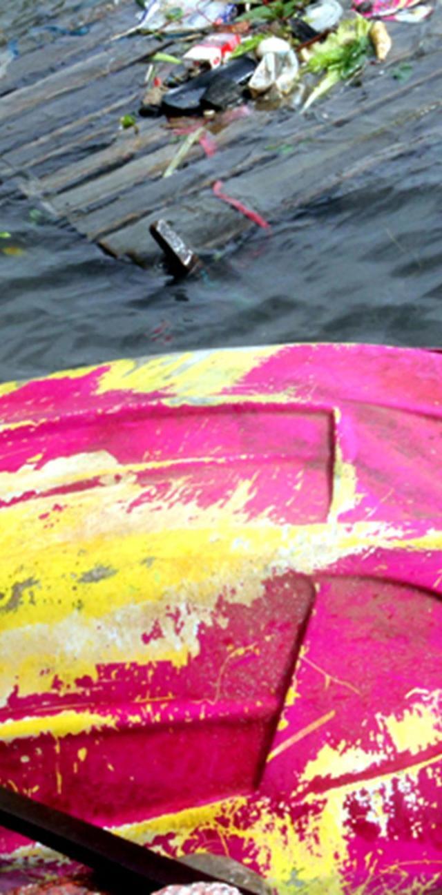 """Một chiếc xuồng du lịch bị vứt bỏ tại bãi biển thị trấn Dương Đông, bên cạnh là một bè gỗ """"chở"""" đầy rác."""