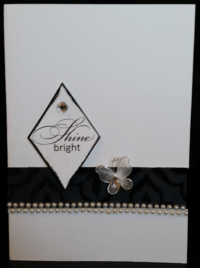 white card with embossed diamond shape message saying shine bright raised mounted above velvet embossed paper and a string of pearls
