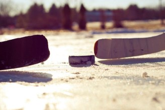 Two hockey players face off on a frozen lake. Tyler / Flickr