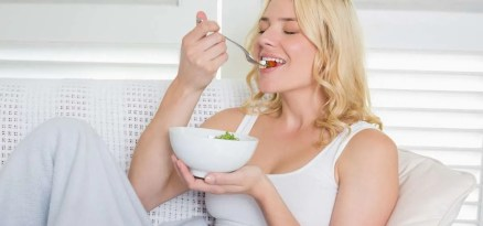 Happy blonde relaxing on the couch eating a salad