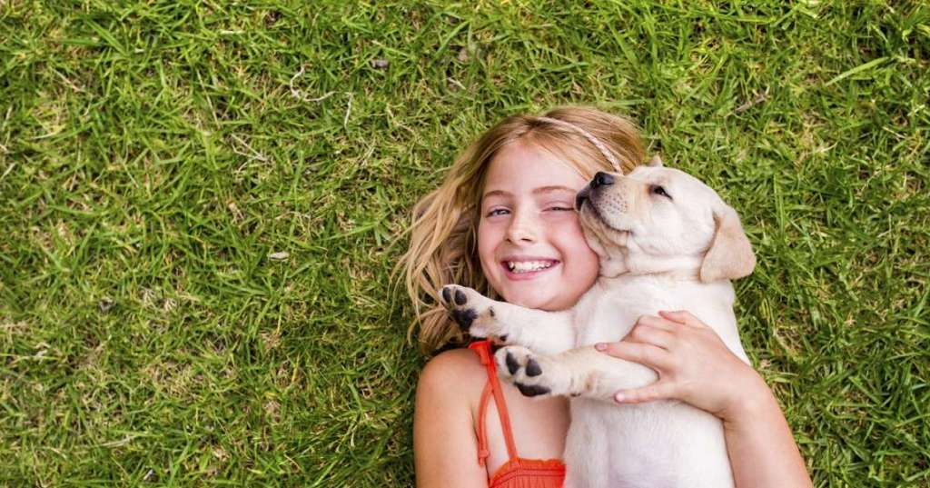 Girl with puppy lying on grass