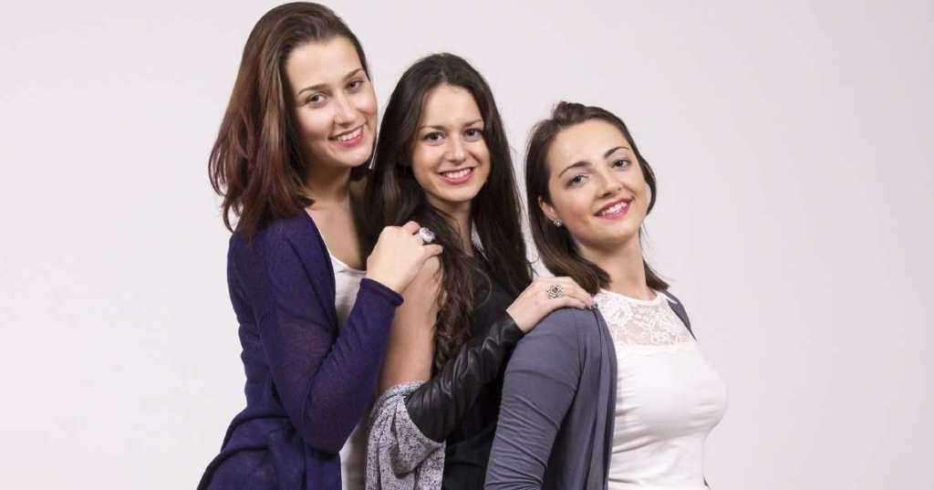 Portrait of three girls, in high heel shoes. Studio shot, white