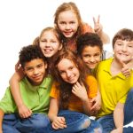 Group of happy 10 years old boys and girls smiling gesticulating and hugging