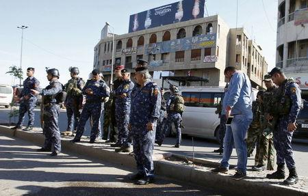 Iraqi security forces gather at the site of a bomb attack in Baghdad Bab Sharji district