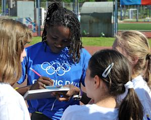 Lucia Kimani (L) signs autographs for young Bosnian…