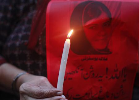 A woman holds a picture of Malala Yousufzai with a candle as she participates in a rally to condemn the attack on Yousufzai, in Karachi October 11, 2012. REUTERS/Athar Hussain