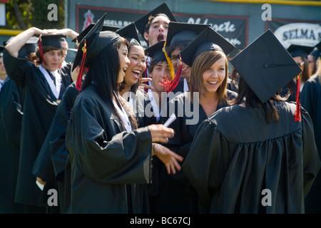 Happy senior high school seniors in cap and gown prepare to graduate
