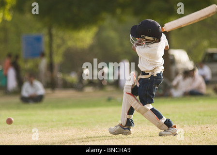 Boy playing cricket in a playground, New Delhi, India Stock Photo