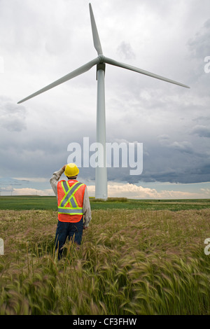 Wind power technician standing next to wind turbine, near Pincher