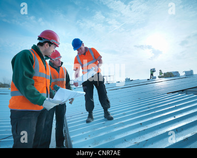 Workers reading blueprints on site Stock Photo 48975768 - Alamy