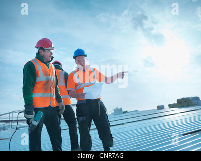 Workers reading blueprints on roof Stock Photo 47839225 - Alamy