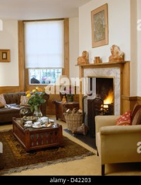 Armchair in front of window in low ceiling cottage living ...
