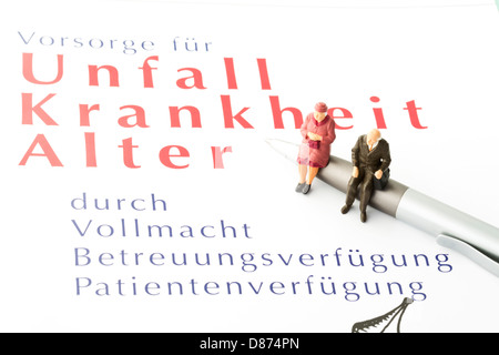 Figurines sitting on pen with advance directive form, close up Stock - advance directive form