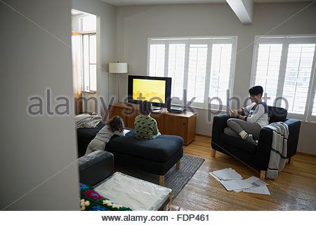 Family relaxing watching TV in living room Stock Photo, Royalty - tv in living room