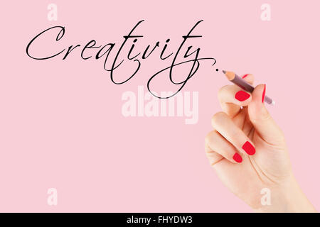 Creative industries Female hand with pencil writing the word Stock