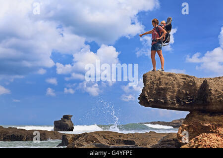 Man Standing On Cliff By Sea Against Sky Stock Photo