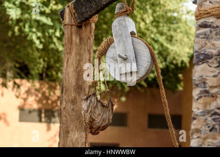 Traditional Wooden Bucket In Old Stone Well Stock Photo