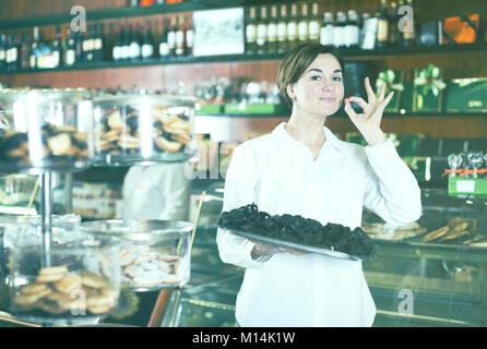 Female shop assistant demonstrating delicious cakes on tray in