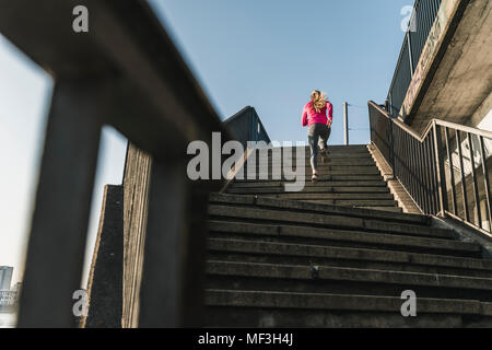 Fit Young Woman Running Up Stairs In Grey Tights And Sport