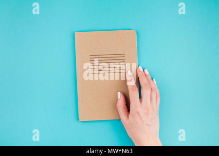 Creative flat lay of woman hands holding craft paper notebook diary