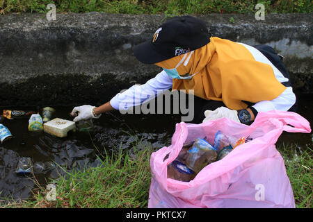 A volunteer seen picking up plastic waste from a drainage World