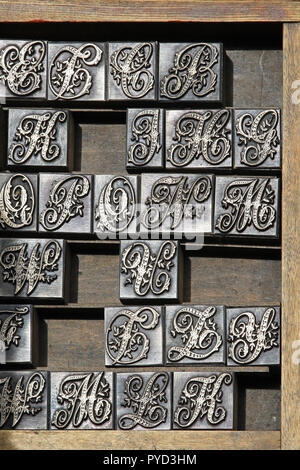 A box of old vintage printing press letter blocks in a old wooden
