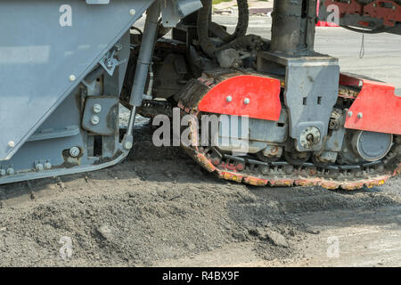 Close view on the workers and the asphalting machines paiving