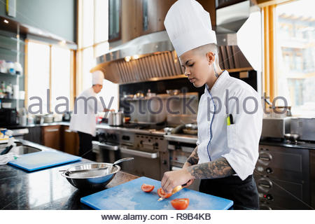Female prep cook slicing tomatoes in restaurant kitchen Stock Photo