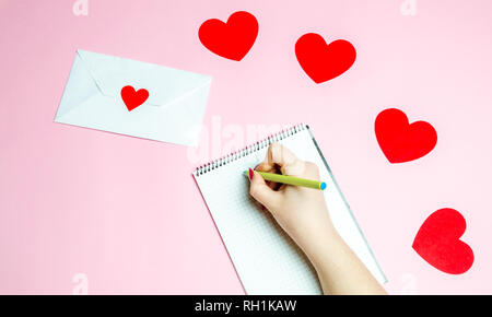 Female hand writing a love letter Valentines day concept Greeting