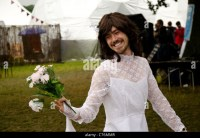 a man in a wedding dress holding flowers at a festival ...