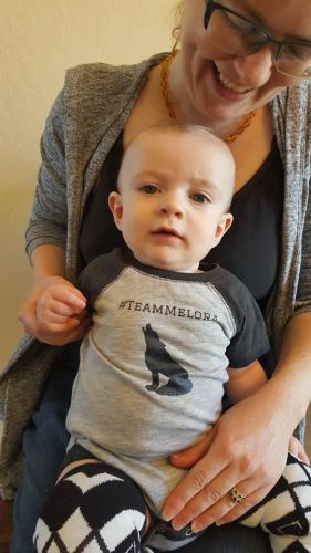 "I made custom shirts for my son that were related to the stories my writers' group members had written. Here, he sports his #TeamMelora onesie, which refers to the love triangle in Marie Zhuikov's books, ""Eye of the Wolf"" and ""Plover Landing."""