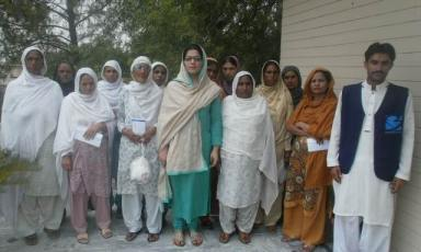 Hina Fysal, Chief Executive, Co-Founder, BMWT with recipients of cash assistance.