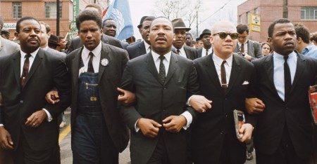 James Forman (blazer/overalls) locks arms with MLK as they enter Montgomery, 1965.