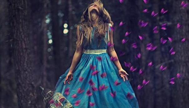 mujer con vestido azul rodeada de mariposas