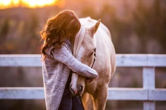 amor a un animal: chica abrazando un caballo