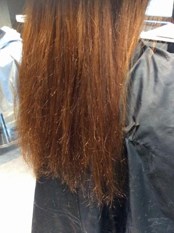 縮毛矯正施術前のビフォーの画像です。黒い毛染めのクロスを着た女性が鏡の前でカット椅子に座って向こうを向いて座っています。斜め後ろから写真を撮りました。髪の毛の状態は毛先が酷いダメージを受けたビビリ毛です。櫛も指も通りません。毛先はビビリ毛に近い状態です。