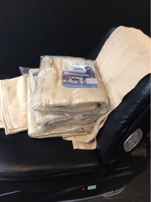 タオルをシャンプーの電動ベッドの上に置いて撮影した。10枚の束がビニール袋の中に入って二個あります。袋から出した10枚の束が一つ五枚とバラで一枚のタオルのかたまりです。