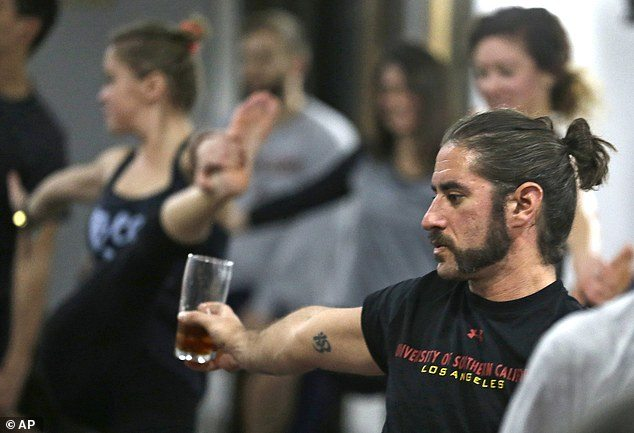 In this Thursday, Dec. 3, 2015 photo, Reed Patterson practices yoga while holding onto his beer at the Platform Beer Co., in Cleveland. Craft breweries are partnering up with yoga studios around the country as more breweries are hosting classes to attract a new crowd to the bars and yoga studios are using the beer to get more men to try yoga. (AP Photo/Tony Dejak)