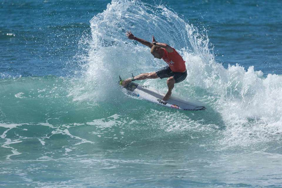 Mick Fanning pulling of a spin trick on the crest of a wave (Niko Labarbera)