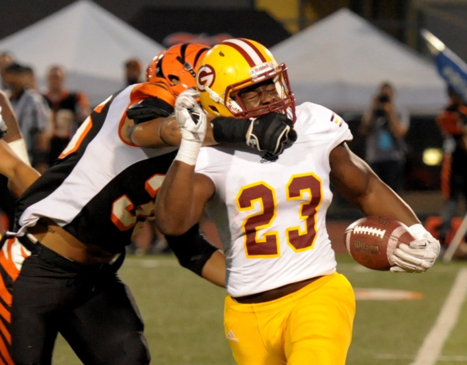 Sophomore running back Myron Buchanan (No. 23, white) gets tackled via his facemask against Riverside City College. (Cliff Robbins)