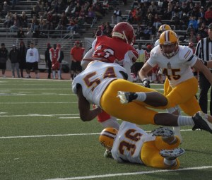 Saddleback's Carlton LaFrance (No. 54, white), Marcus Meredith (No. 36, white) and Anthony Hickey (No. 45, white) attempt to tackle a Rams player. The Gauchos fell to City College of San Francisco, 26-14 losing a chance at a state and national championship. (Cliff Robbins)