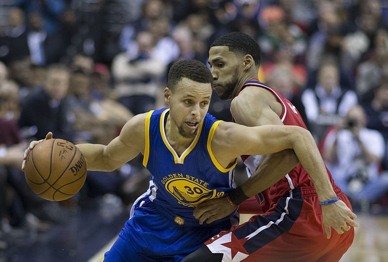 Golden State Warriors star Steph Curry (30) spins away from Garrett Temple's defense at an away game against the Wizards on February 3 2016. (By Keith Allison from Hanover, MD, USA (Stephen Curry) [CC BY-SA 2.0 (http://creativecommons.org/licenses/by-sa/2.0)], via Wikimedia Commons)