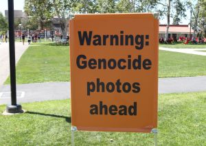 """Signs were posted around Saddleback College's campus saying """"Warning: Genocide photos ahead."""" In the background, students and others gather in front of the pro-life display. (Nick Nenad/Lariat)"""