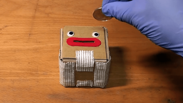 A Cardboard Coin Box With A Cute Face That Blasts Open
