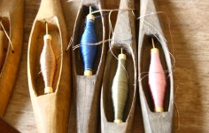 Picture of several tapestry bobbins with different colors of thread.