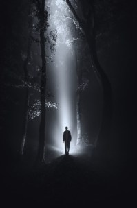 Image of someone walking toward a light coming down from above through intense darkness.